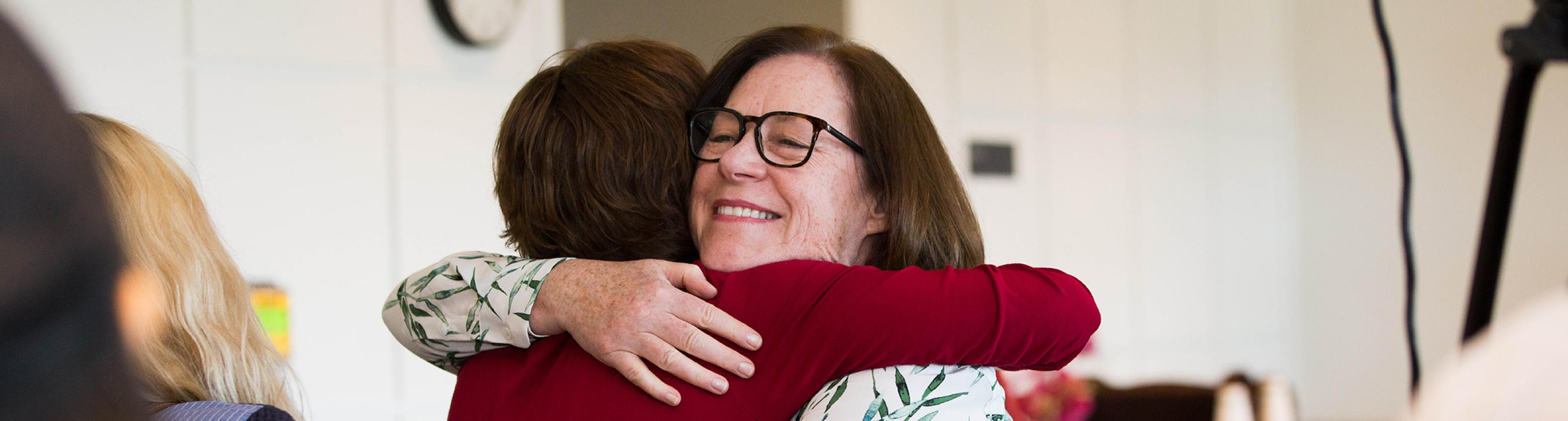 former caregiver hugs Margaretta Page, nurse coordinator for the UCSF Caregiver Program