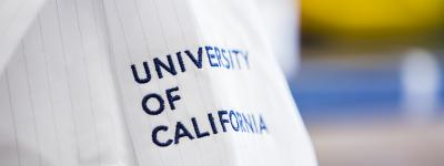 "white lab coat embroidered with ""University of California"" hangs in a laboratory space"